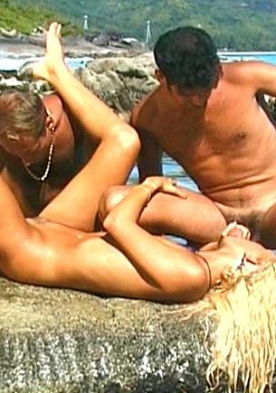 Suzan neukt met twee mannen in de branding